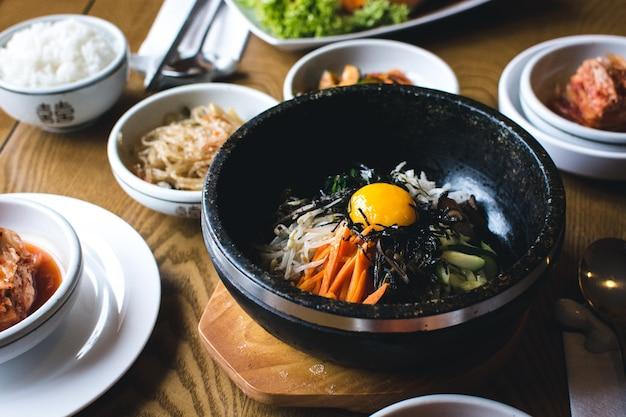 Traditional korean bibimbap vegetables with raw egg yolk Free Photo