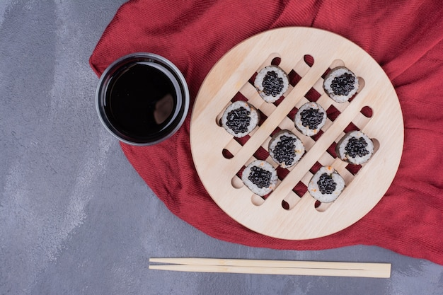 赤いテーブルクロスに箸と醤油をかけた伝統的な巻き寿司。 無料写真