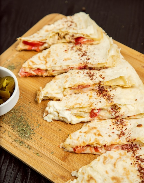 Traditional meat vegetable gutab, qutab, gozleme on wooden board with sumakh, turshu . Free Photo