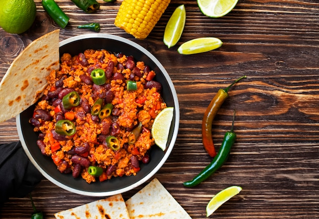 Traditional mexican chili con carne served on a rustic wooden table in a pan with corn, mexican tortilla bread, lime and jalapeño. top view. Premium Photo
