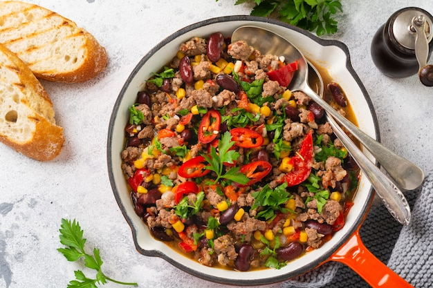 Traditional mexican food - chili con carne with minced meat and vegetables stew in tomato sauce in a cast iron pan on light gray slate or concrete table. top view with copy space. Premium Photo