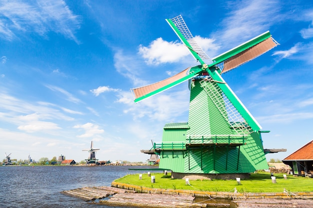 Traditional old dutch windmill against blue cloudy sky in the zaanse schans village, netherlands. Premium Photo
