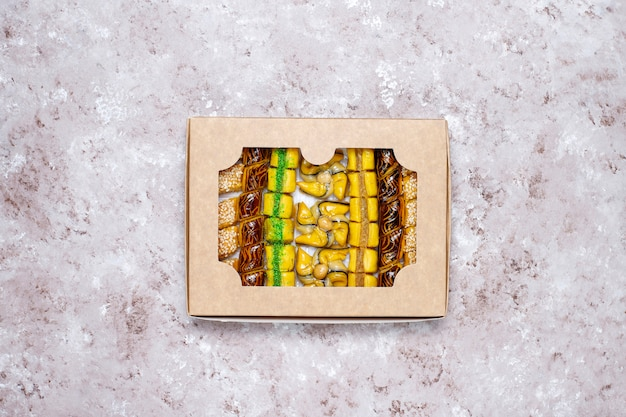 Traditional oriental sweets with different nuts on concrete  background, top view, copy space Free Photo