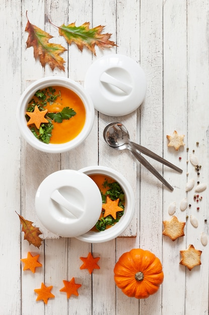 Traditional pumpkin homemade cream-soup with seeds, crackers and little pumpkin. Premium Photo
