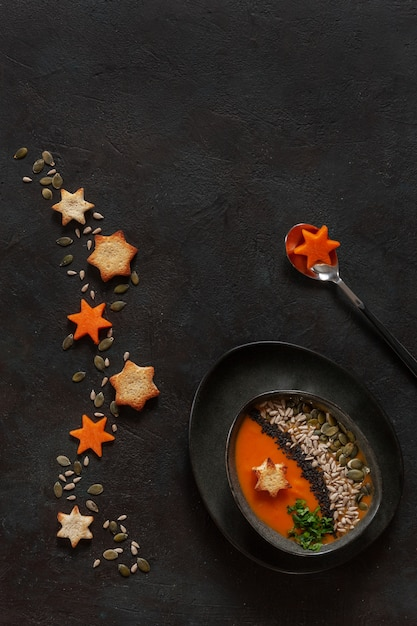 Traditional pumpkin homemade cream-soup with seeds and crackers. Premium Photo