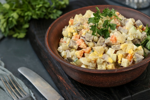 Traditional russian festive salad olivier with tongue in a bowl against a dark background, horizontal orientation Premium Photo