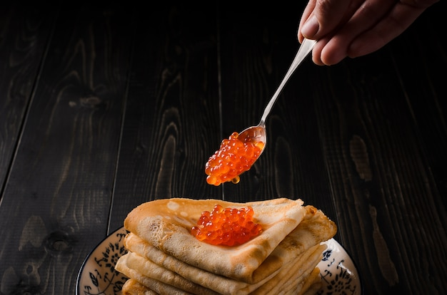 Traditional russian pancakes with red caviar with a silver teaspoon red caviar is placed on a stack of pancakes. Premium Photo