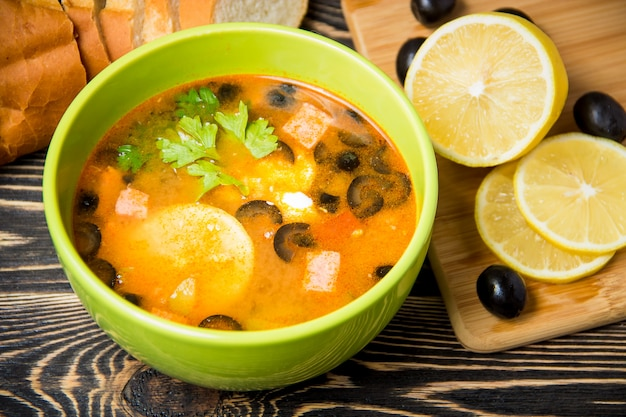 Traditional russian soup solyanka in bowl on the table Premium Photo