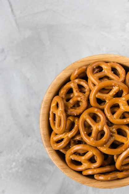 Traditional salty mini pretzels in wooden bowl on a gray backround. Premium Photo