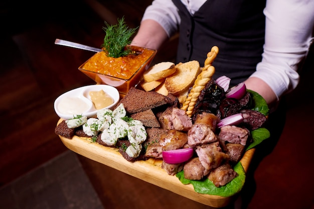 Traditional sausage, toasts, lard and sauce on a wooden tray. Premium Photo