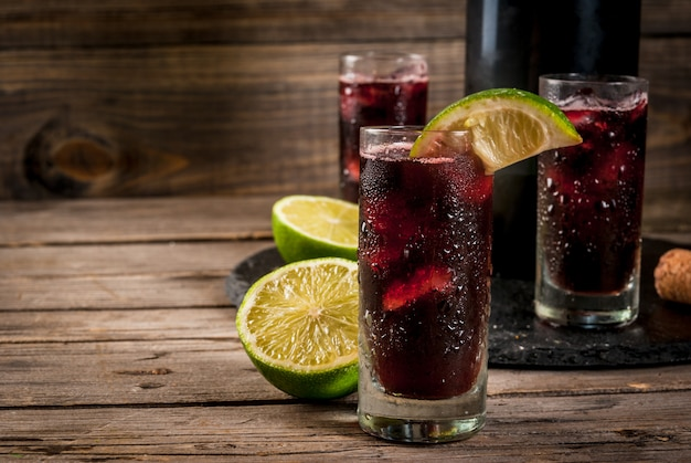 Traditional spanish alcoholic drink cocktail calimocho with wine cola lime juice and ice decorated with pieces of lime Premium Photo