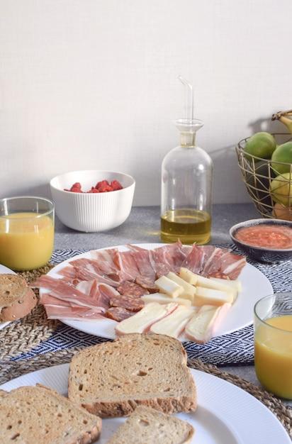 Traditional spanish breakfast jamon cheese toasted bread tomato olive oil orange juice copy space Premium Photo