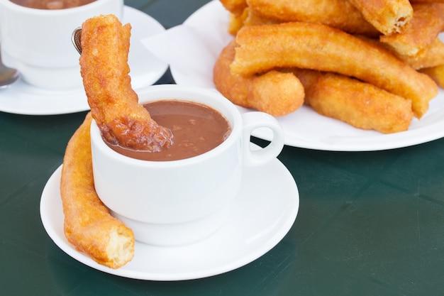 伝統的なスペインのペストリー-チュロスとチョコレートのカップ Premium写真