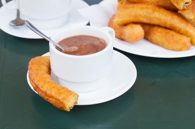 伝統的なスペインのペストリー-チュロスとチョコレートの白いカップ Premium写真