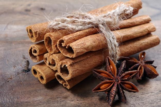 Традиционные специи для глинтвейна. палочки корицы и аниса звезды на деревянном столе. Premium Фотографии