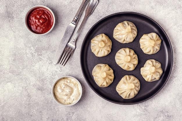 伝統的な蒸し餃子khinkaliトマトとタルタルソース添え Premium写真