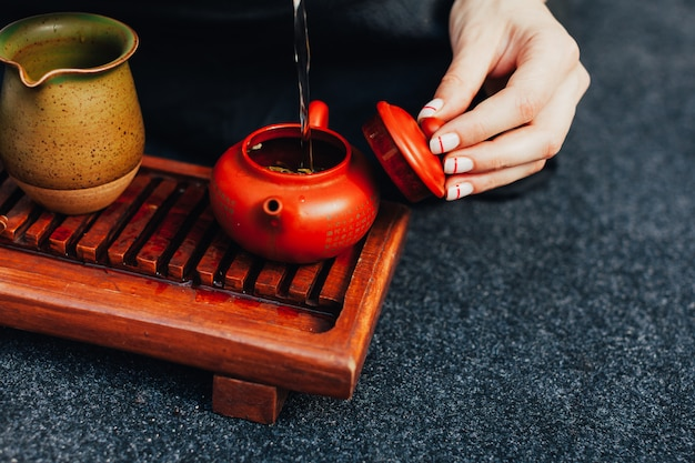 Traditional tea ceremony close up with woman hand Premium Photo