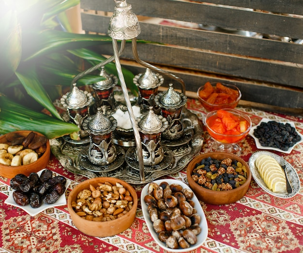 Traditional tea setup with antique tea tray and glasses and dry fruit bowls Free Photo