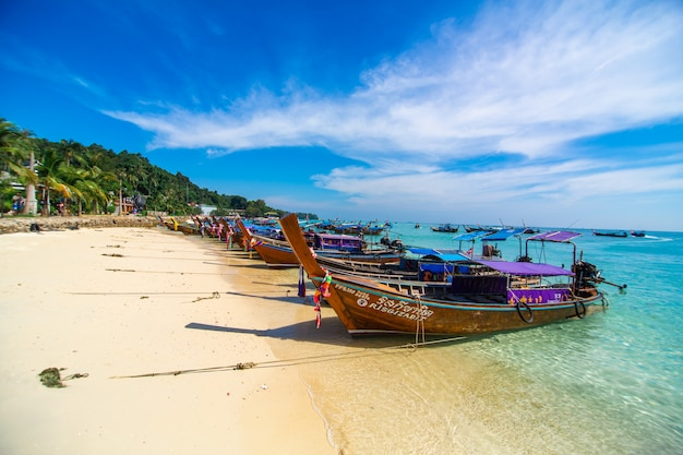 Traditional thai fishing wooden boats wrapped with colored ribbons. at sand coast of tropical island. Premium Photo
