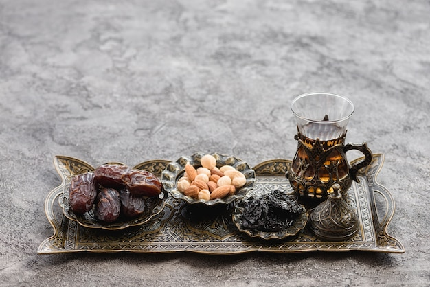 Traditional turkish arabic tea glasses; dates and nuts on metallic tray over the concrete backdrop Free Photo