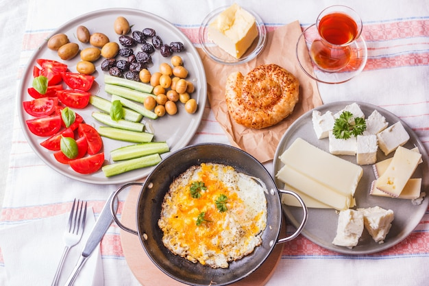 Traditional turkish breakfast - fried eggs, fresh vegetables, olives, cheese, cake and tea Premium Photo