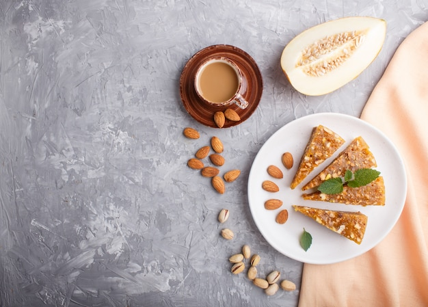 Traditional turkish candy cezerye from caramelised melon, pistachios on white plate and a cup of coffee Premium Photo