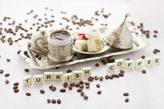 Traditional turkish coffee and sweets in silverware. lettering turkish coffee Premium Photo