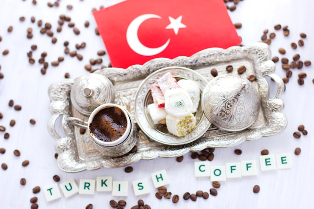 Traditional turkish coffee and sweets in silverware with flag of turkey. lettering turkish coffee Premium Photo