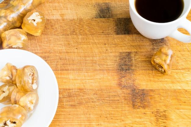 ヘーゼルナッツのトップビューで伝統的なトルコ料理ロクム。甘いアラビア語のデザートと木製の背景にブラックコーヒーのカップ Premium写真