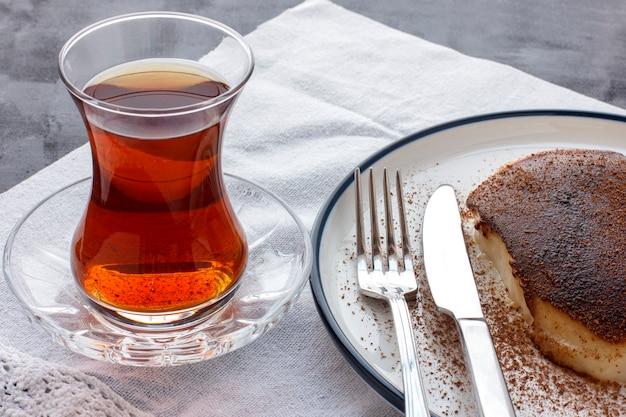 Traditional turkish dessert kazandibi with ground cinnamon and turkish tea Premium Photo