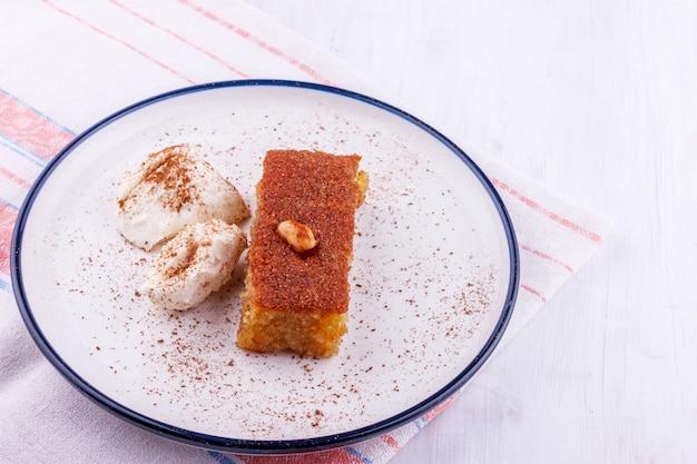 Traditional turkish dessert - sambali, sambaba or damascus with cream and cinnamon powder Premium Photo