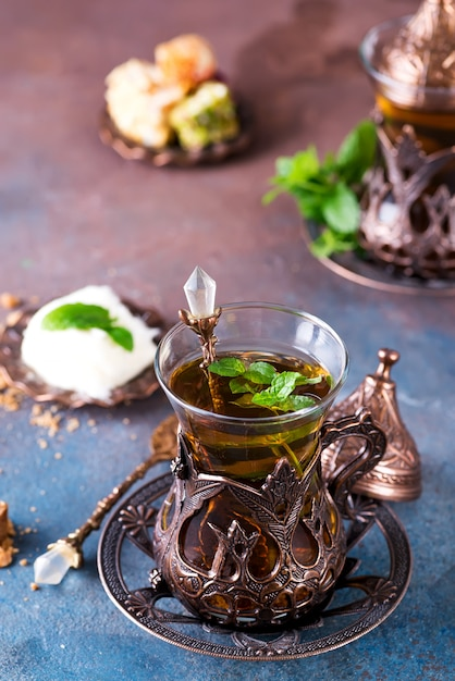 Traditional turkish tea with mint leaves and sweets in a traditional glass on concrete Premium Photo