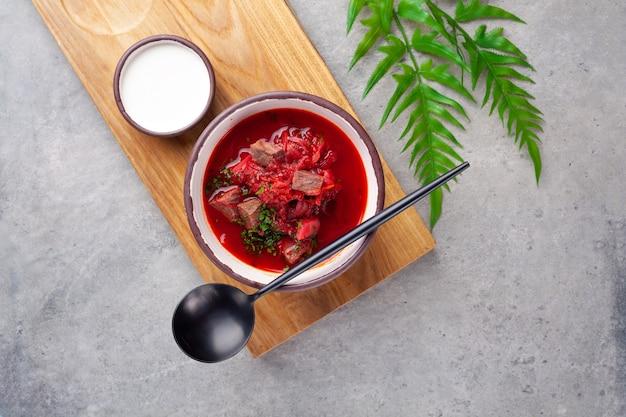 伝統的なウクライナ料理とロシア料理のボルシチ、ビーツ、牛肉、サワークリーム、灰色のテーブル、クローズアップ、上に木の板にスプーンの赤いスープ Premium写真