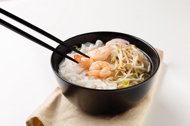 Traditional vietnamese noodle soup pho with shrimps in black bowl Premium Photo