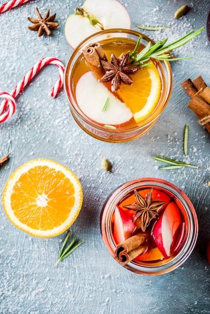 伝統的な冬の飲み物、白と赤のホットワインカクテル、白と赤のワイン、スパイス、リンゴ、オレンジ。水色のテーブルの上に、 Premium写真