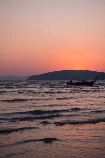 Traditional wooden thai long-tail passenger boat on sea in evening Free Photo
