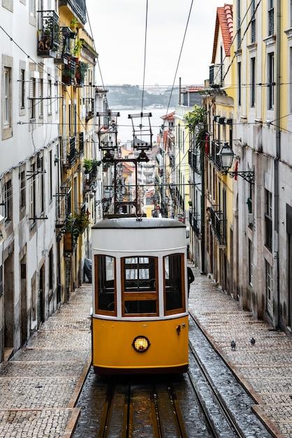 Традиционный желтый трамвай на узкой улочке в лиссабоне в дождливый зимний день на фоне реки тежу, расфокусированной на заднем плане. Premium Фотографии