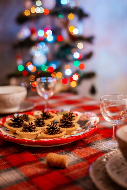 Traditionally decorated christmas table. creative decoration of the festive table cones on a plate on the background of bokeh lights. Premium Photo