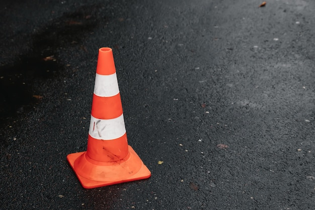 Traffic cone, with white and orange stripes on gray asphalt Premium Photo