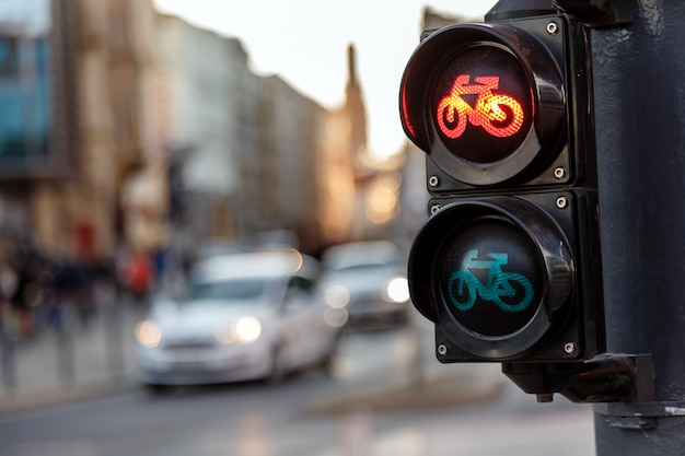 Traffic lights for bicycles lights red on a background of moving cars in the evening on a city street Premium Photo