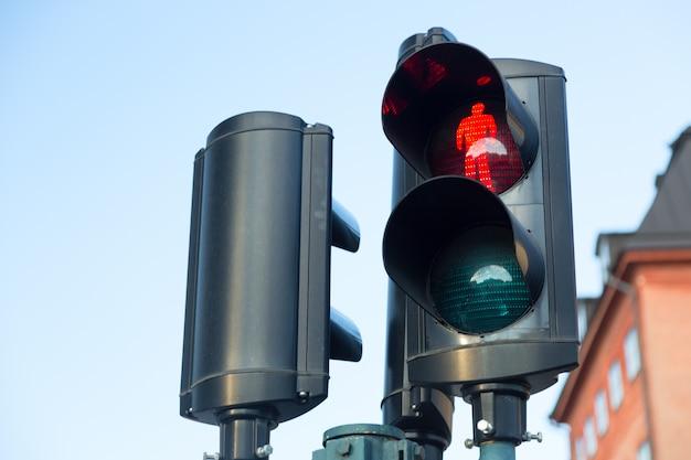 スウェーデン、ストックホルムの空を背景に歩行者に赤信号が点灯している信号機 Premium写真