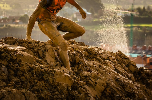 Trail running athlete crossing the dirty puddle in a mud racer. Premium Photo