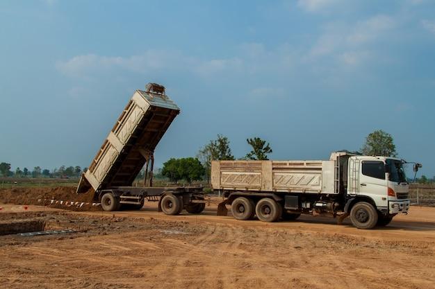 Trailer Dump Truck Unloading Soil Or Sand At Construction Site Premium Photo