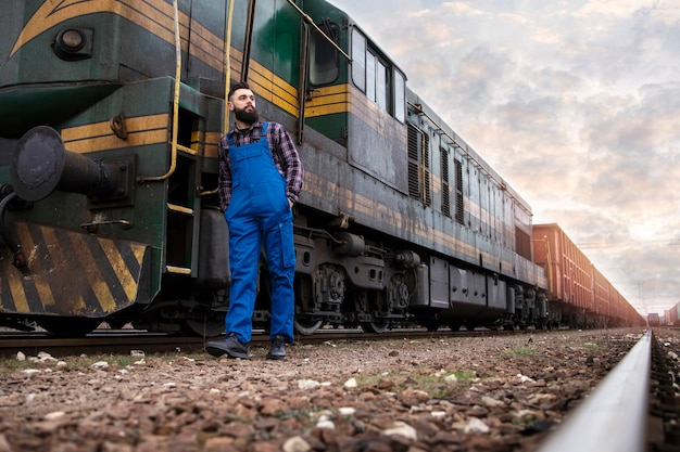 Train driver standing by locomotive at railroad station Free Photo