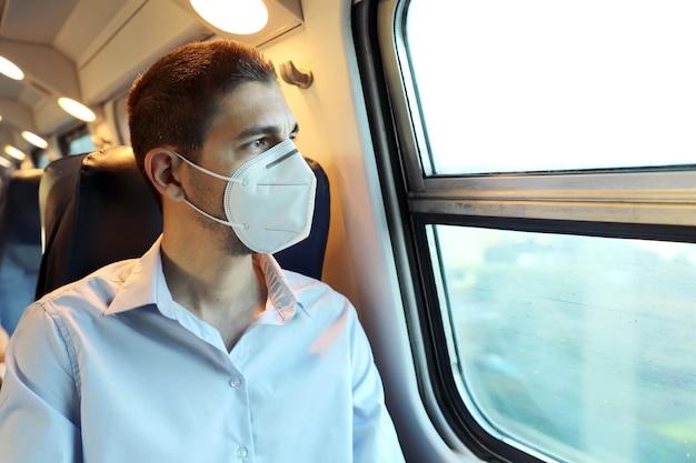 Пассажир поезда с защитной маской, глядя в окно Premium Фотографии