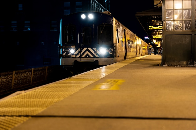 Train passing by station at night Free Photo