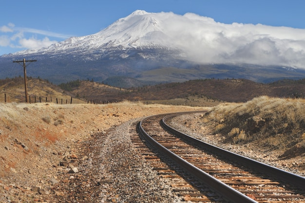 Train tracks in the middle of an empty field with a snowy mountain in the distance Free Photo