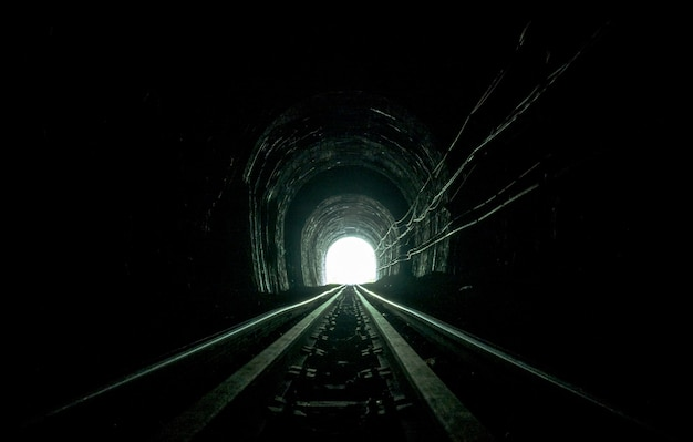 Train tunnel. old railway in cave. hope of life in the end of the way. Premium Photo