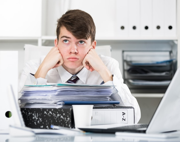 trainee near the pile of documents and cup Free Photo