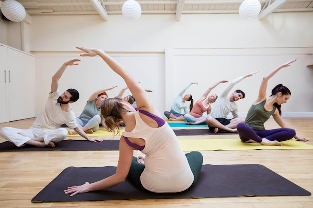 Trainer assisting group of people with stretching exercise Free Photo